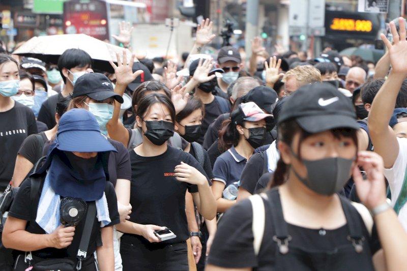 港人遊行抗議禁蒙面法 見鏡頭頻閃避