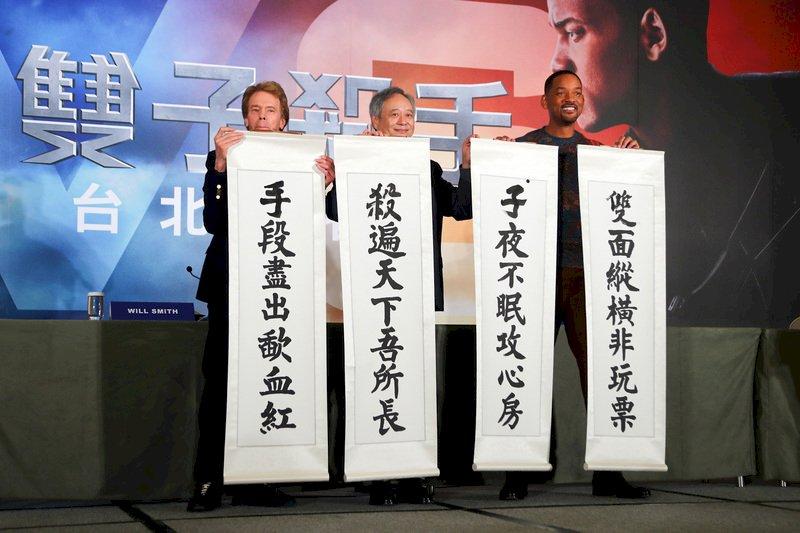 導演李安(中)與美國男星威爾史密斯(Will Smith)(右)、製片傑瑞布魯克海默(Jerry Bruckheimer)(左)21日在台北同為新片「雙子殺手」宣傳造勢,3人揮毫寫下藏頭對聯,預祝電影票房長紅。