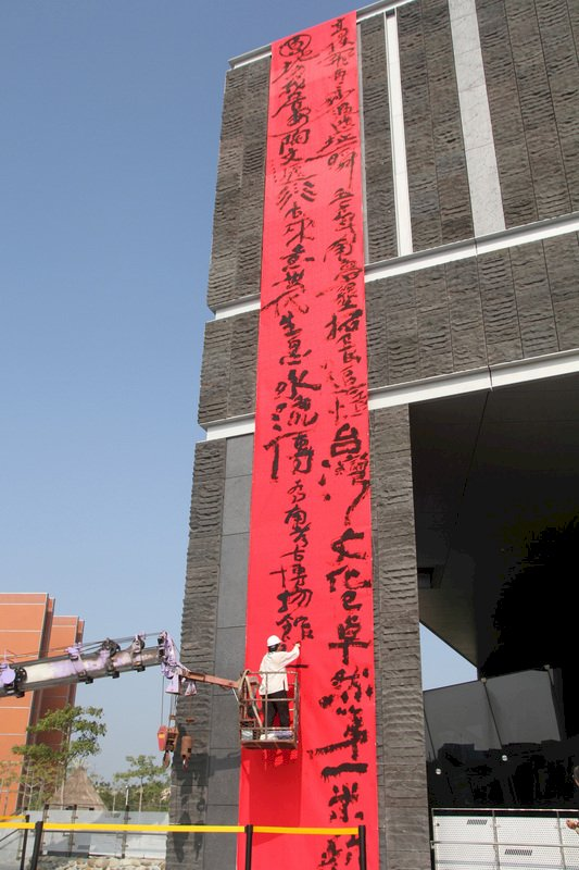 國立台灣史前文化博物館南科考古館19日邀請意象書法家陳世憲進行創作,在館外牆的大型紅色絹布上書寫詩句。