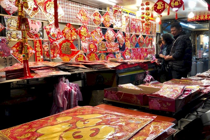 農曆春節將至,民眾著手準備年貨,20日晚間民眾在一處攤販前採買春聯。