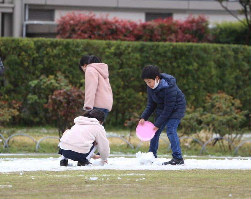 受到低氣壓和寒氣影響,29日凌晨到中午過後,日本關東地區下雪,東京市中心時隔32年在3月底觀測到積雪。圖為芝公園孩童外出玩雪。