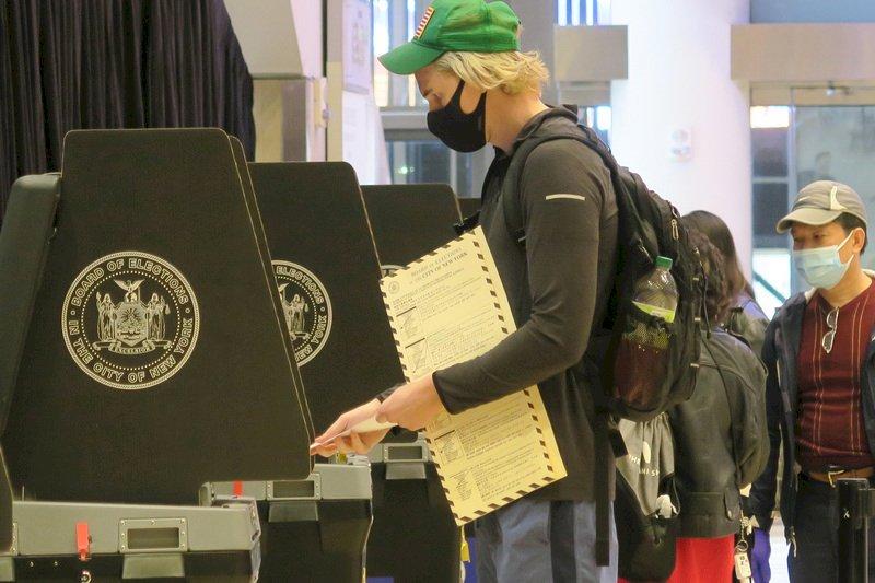 美國總統大選倒數,提前投票的紐約選民美東時間28日在麥迪遜花園廣場大廳的投票所使用選票掃描器。