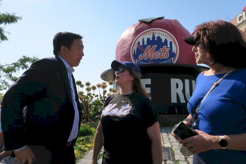 紐約市長初選投票前夕,參選的台裔企業家楊安澤(左)美東時間21日在大都會隊主場花旗球場外與球迷互動。 (圖:中央社)