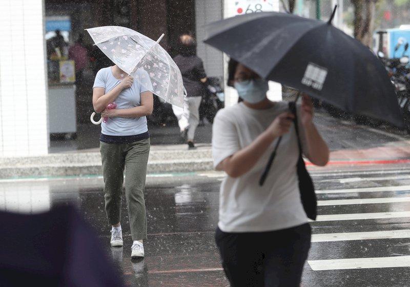 中央氣象局24日表示,基隆北海岸、東半部及大台北地區有局部短暫雨發生的機率,台北市區午後降下陣雨,民眾撐傘遮擋雨勢。中央社記者吳家昇攝  110年9月24日 (圖:中央社)